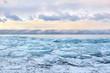 Field of blue transparent hummocks on the frozen Lake Baikal. Sunset sky.