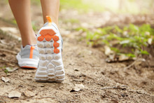 People And Sports. Athletic Pair Of Female Legs In Running Shoes On Trail. Young Attractive Woman Jogger Walking Or Hiking In Forest Or Park, Preparing For Sprint Or Marathon. Selective Focus On Sole
