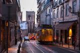 Fototapeta Uliczki - Tram car crossing street at evening in Lisbon, Portugal