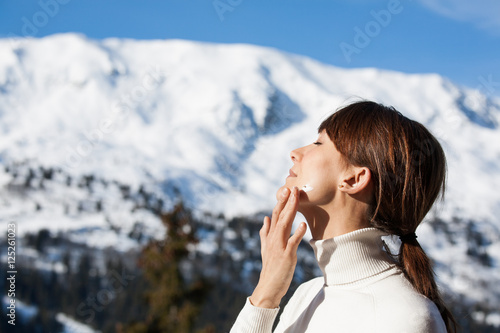 portrait d'une belle femme qui s'applique de la crème solaire en hiver