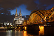 Illuminated cologne cathedral and bridge after sunset with blue sky and dark clouds