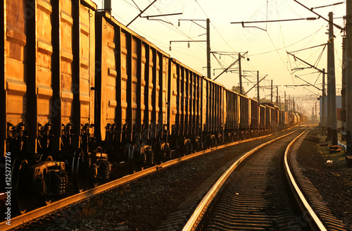Fotografering Freight train moving on the tracks at sunset