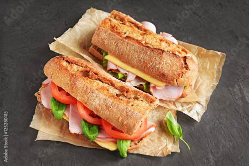 Sandwich with ham, tomato, cheese and basil close up
