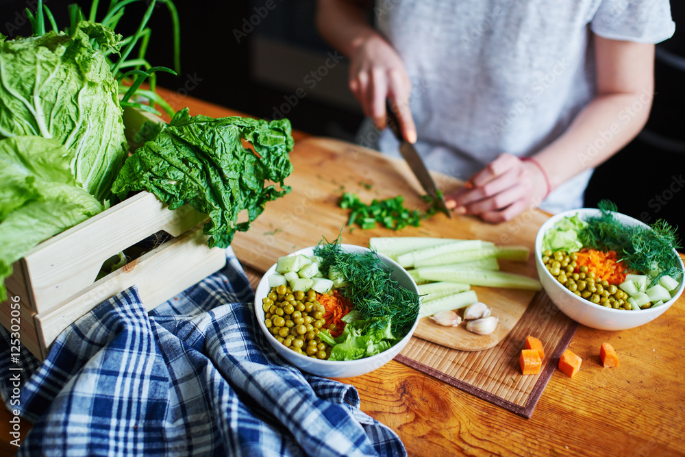 Fototapety, obrazy: Bowl with green peas, cucumbers, carrots, lettuce and dill standing on a table on a background of hand chopping green onions with knife on wooden Board