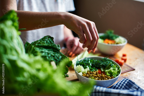Fototapeta Female hand pours green onions in a bowl with green peas, cucumbers, carrots, lettuce and dill standing on a table obraz