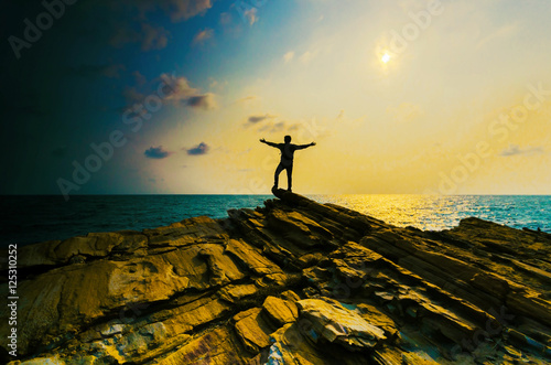 man hand up on the top stone with the sunset over sea. Canvas Print