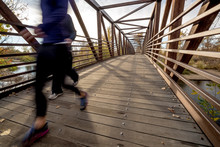 Monring Run Across A Foot Bridge With Autumn Trees