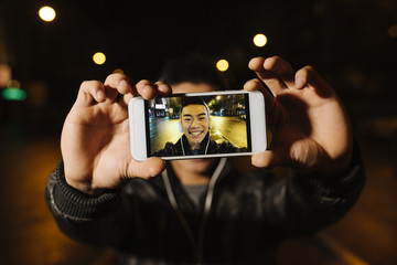 Fototapeta Young asian man taking a selfie in the city.