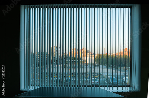 Fotografia  City view  through the vertical blinds window decoration in interior of dark roo
