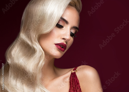 Photo  Beautiful blonde in a Hollywood manner with curls, red lips, red lingerie