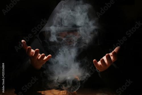 Fotografie, Obraz man in a black hood with cristal ball