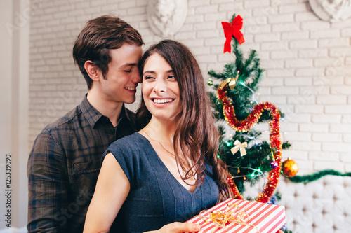 Family Christmas Gift Giving.Smiling Man Hugs His Girlfriend With Present Christmas Gift