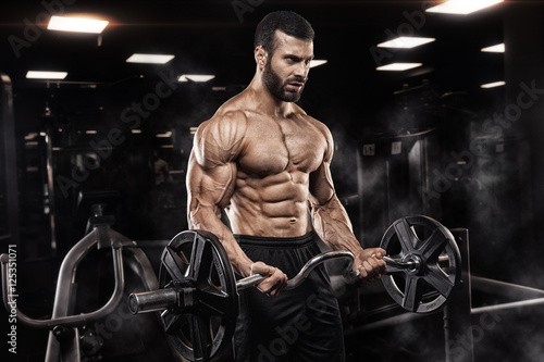 Handsome man with big muscles, posing at the camera in the gym Wallpaper Mural