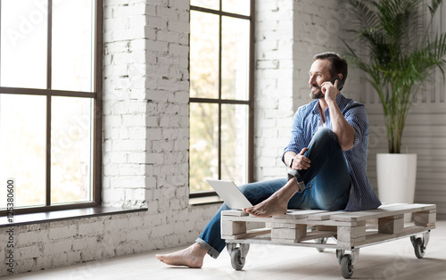 Photo  Positive good looking man speaking on the phone