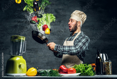Fotografie, Obraz  Man cook holds a pan with vegetables flying in the  air.