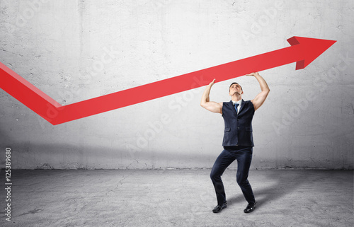 Fotografía  Muscular businessman full-height in jacket without sleeves holding big red arrow