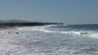 A dozen of surfers at a surf spot at the Canary Islands paddling out in the waves, some trying to catch a wave, some in line ready for a take off.