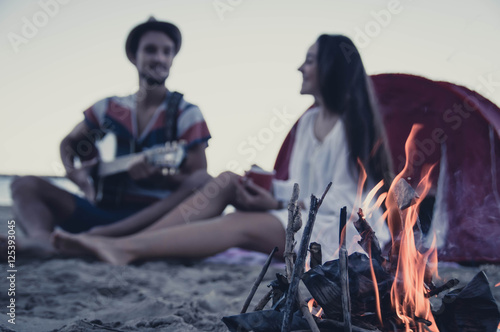 Poster Muziekwinkel Happy young couple sitting near campfire and playing guitar