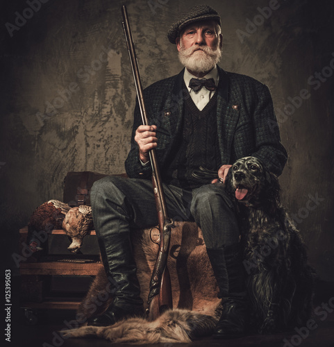 Senior hunter with a english setter and shotgun in a traditional shooting clothing, sitting on a dark background Wallpaper Mural