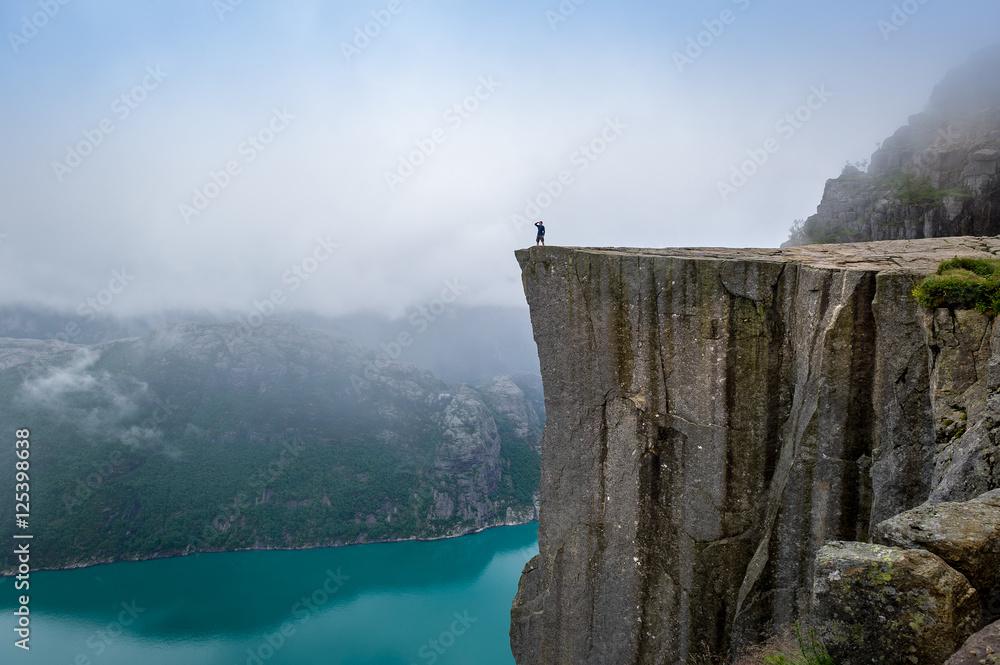 Fototapety, obrazy: Tourist standing at Prekestolen rock's edge.