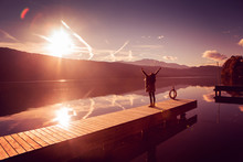 Woman With Arms Wide Open On A Lake In Sunset