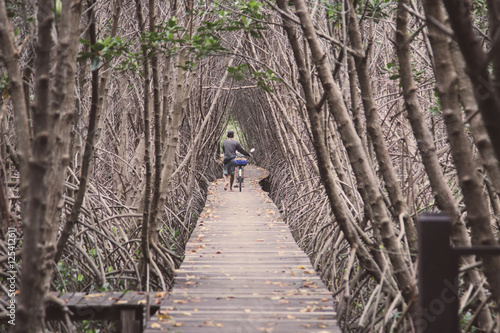 Old man walking on the bridge in mangrove forest with wood walkway
