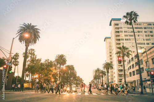Foto auf Leinwand Los Angeles Locals and tourists walking on zebra crossing and on Ocean Ave in Santa Monica after sunset - Crowded streets of Los Angeles and California state - Warm desat twilight color tones with blurred people