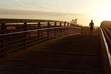 Jogging To The Light-a Lone Female Jogger Jogs Across A Footbridge, Toward A Low Setting Sun