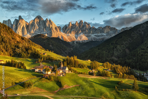 Foto  Santa Maddalena village in front of the Geisler or Odle Dolomites Group on sunset, Val di Funes, Italy, Europe