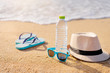 Vacation concept. Essentials on the sea beach. Bottle of drinking water, sunglasses, hat, flip-flops.