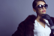 Portrait Of Glam Dark-haired Model In Stylish Classic Sunglasses Wearing White Blouse, Sable Coat And Set Of Luxurious Bracelet And Silver Chain With Pendant. Eyewear Concept. Studio Shot. Copy-space