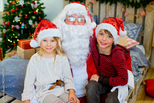 Spoed Fotobehang Carnaval Santa Claus and two children sitting on the bed
