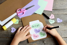 Child Doing A Birthday Card. Child Holds A Black Marker In Hand And Writes. Paper Greeting Card With Jar, Hearts And Wishes. Scissors, Colored Paper Sheets, Glue Stick On Wooden Background. Kids Art