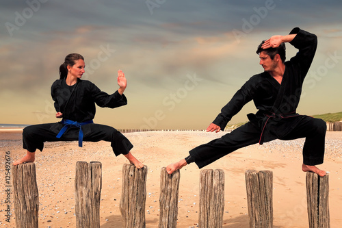 Foto op Plexiglas Vechtsport Two martial arts fighters practicing combat sport on the beach poles: man and woman doing a Karate - Viet Vo Dao posture
