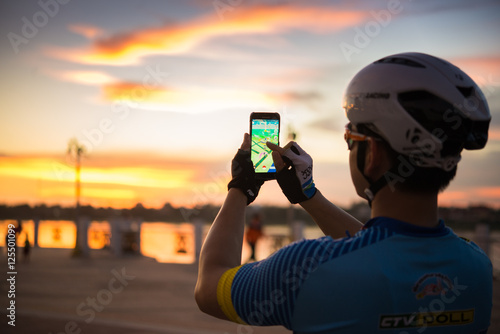 NONGKHAI, THAILAND - AUGUST 09 2016 : Male hand holding a  smartphone with a running Pokemon Go application at sunset Wallpaper Mural