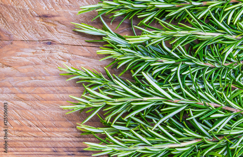Fresh rosemary on wood background copy space.