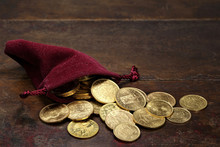 Various European Circulation Gold Coins From The 19th/20th Century In A Velvet Purse On Rustic Wooden Background