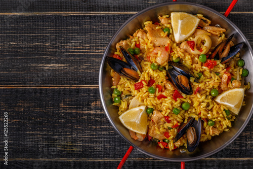 Paella with chicken,  seafood, vegetables and saffron served in