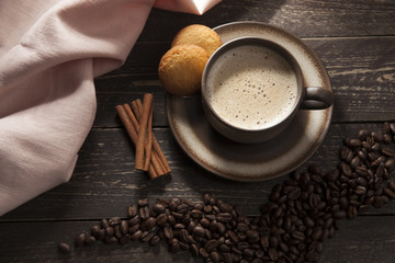 Fototapeta Do kawiarni Coffee background. Ground coffee with foam with coffee beans on a wooden dark table with cinnamon sticks and butter shortbreads.