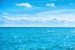 Leinwandbild Motiv Sea water and blue sky with white clouds