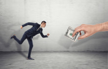 Businessman Running For Big Man Hand Luring With Dollar Bill