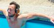 Mann hört im Pool Musik