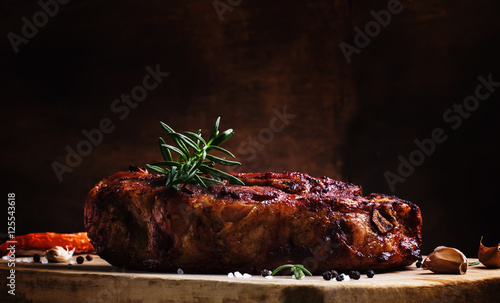 Valokuva  Baked pork shoulder with pepper, rosemary and garlic, vintage wo