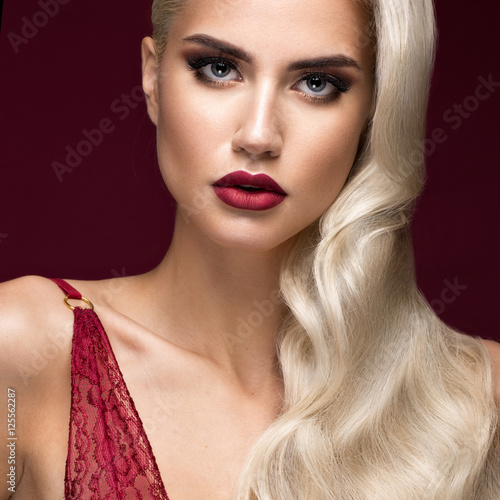 Beautiful blonde in a Hollywood manner with curls, red lips, red lingerie плакат