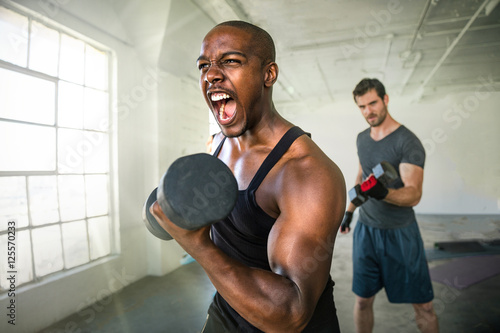Cuadros en Lienzo Determined endurance work out man shouts success after bicep curl fitness exerci