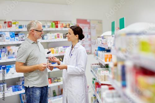 Photo sur Toile Pharmacie pharmacist and senior man buying drug at pharmacy