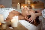Young beautiful girl having face massage relaxing in spa salon.