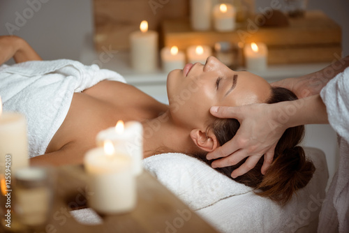 Fotografia  Young beautiful girl having face massage relaxing in spa salon.