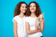 canvas print picture - Two girls twins smiling, winking, showing like over blue background.