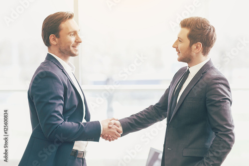 Fotografía  Two handsome colleagues shaking hands in an office.